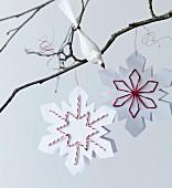 Papiersterne mit gestickten Details hängen an einem Zweig mit Dekovogel