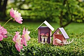Bird figurine and roses in wto hand-crafted cardboard houses in garden