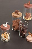 Animal-shaped biscuits in storage jars with matching animal figurines
