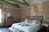 Stone walls, green-painted roof beams, antique chest of drawers and quilted bed cover in Mediterranean bedroom