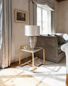 Table lamp on Art-Deco side table in luxurious interior with antique furniture