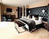 Maskulines Schlafzimmer mit schwarz gepolstertem Betthaupt, Bettbank und Lesesessel