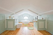 Custom fittings and bathroom suite in white and pastel green in large attic bathroom with rustic ambiance