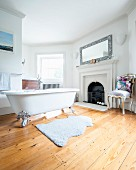 Free-standing bathtub with silver-gilt claw feet on wooden floor in spacious bathroom with open fireplace