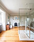 Shower in modern, glass cubicle in spacious, rustic bathroom