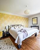 Ländliches Schlafzimmer mit Doppelbett vor tapezierter Wand mit floralem Muster auf gelbem Grund