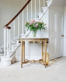 Neoclassical-style, gilt console table at foot of staircase in foyer