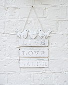 Romantic, white, shabby-chic metal sign decorated with bird figurines hung on wall