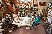 View down onto sculptor at workbench making sculptures and masks in workshop