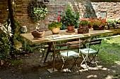 Holztisch mit Blumentöpfen und schlichte Klappstühle vor Ziegelmauer im Innenhof