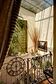 Sunlight falling through skylight into Mediterranean stairwell with wrought iron balustrade and jumble of ornaments on windowsill