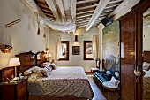 Traditional bedroom with rustic wood-beamed ceiling, antique furniture and double bed flanked by table lamps on bedside tables