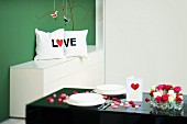 Hand-sewn scatter cushion with lettering reading 'LOVE' in background; set table decorated with heart ornaments and flowers in foreground