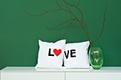 Hand-sewn scatter cushions with lettering reading 'LOVE' next to green glass vase