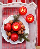 Fir twigs, nuts, pomegranates and apple-shaped candles on plate