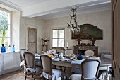 Long, oval dining table and antique upholstered chair in rustic yet stylish dining room