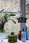 Vase of flowers, vintage glass bottles and soda siphon bottles on sill of lattice window