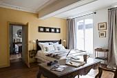 Schlafraum mit gelben Wänden, Doppelbett und antikem Schreibtisch