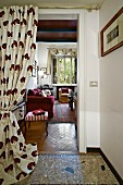 Gathered curtain on open doorway with view into living room with antique footstool and dark red couch