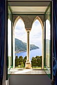 Façade element with pointed arches and Corinthian column behind open window with view of coastal landscape (Villa Cimbrone Hotel)