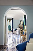 View from foyer through arched doorway of pale armchair in adjoining room with continuous, ornate tiled floor (Villa Cimbrone Hotel)