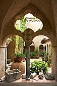 Blick durch Arkaden in Innenhof der italienischen Villa Cimbrone, auf Boden Pflanzentöpfe