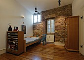 Spartan child's bedroom with rustic stone wall and old wooden floor