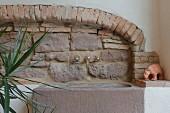 Rustikale Natursteinwand aus Sandstein und Backstein, Steinwaschbecken mit nostalgischen Armaturen