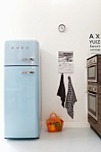 Pale blue retro fridge in modern kitchen with orange plastic basket on floor