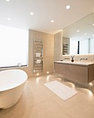 Free-standing bathtub and recessed spotlights in floor and ceiling in bright bathroom