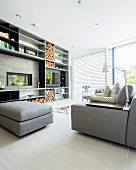 Large fitted shelving unit with integrated fireplace and firewood store in modern living room