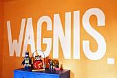 Botschaft auf orangefarbener Wand, davor teilweise sichtbarer blauer Schrank mit Vintage Spielsachen