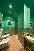 Modern bathroom with shiny mosaic tiles in various shades of green combined with walls and ceiling painted green