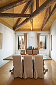 Dining area with rustic wooden table and pale, loose-covered chairs below exposed wooden roof beams