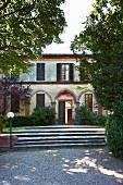 Kiesweg und breite Stufen zu historischem, italienischen Landhaus mit Ziegelbögen und Fensterläden