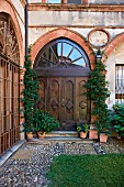 Carved double door in ogee arch and and climbing plants in terracotta pots on front steps