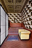 Modern, white cupboards with sliding doors and pastel yellow sofa at foot of staircase with terracotta red dado, expressive, graphic pattern on walls and old, coffered ceiling