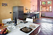 Open-plan, loft-apartment kitchen and modern, white dining area in old Castello decorated in complementary colours