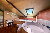 Modern, oval bathtub with massage jets in modern bathroom with sloping ceiling in Italian shades of terracotta