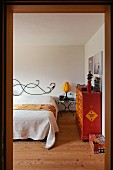 Bedroom with hand-crafted headboard, bedside table and ethnic chest of drawers painted orange and red in prefabricated house