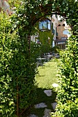 Veew through climber-covered arched doorway leading to seating on lawn in courtyard of Villa Cimbrone in Italy