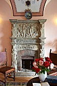 Vase of roses on table in front of open fireplace with carved stone surround (Hotel Villa Cimbrone)