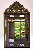 Reflections in antique mirror with ornate metal frame on wall (Villa Cimbrone)