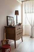 Wooden chest of drawers with tall legs next to draped lace curtain on window in simple, rustic bedroom