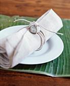 Leinenserviette mit Steindekoration auf weißem Teller, darunter ein Bananenblatt als Tischset