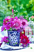 Bouquet of pink dahlias in silvered glass vase on table outdoors
