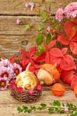 Autumnal still-life arrangement with squash, leaves & flowers