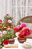 Summery terrace with wicker chair & vase of dahlias on table