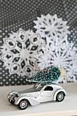 Toy car with Christmas tree on roof in front of paper snowflakes