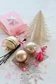 Weihnachtskugeln und rosa Perlen zwischen selbstgemachten Weihnachtsbäumchen aus Papier